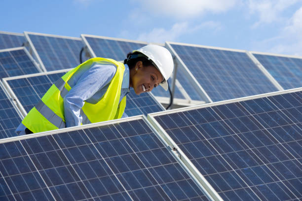 Electrical engineer woman checking solar photovoltaic panels on the roof of a solar farm.